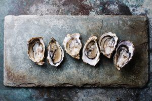 Open Oysters on gray stone plate background