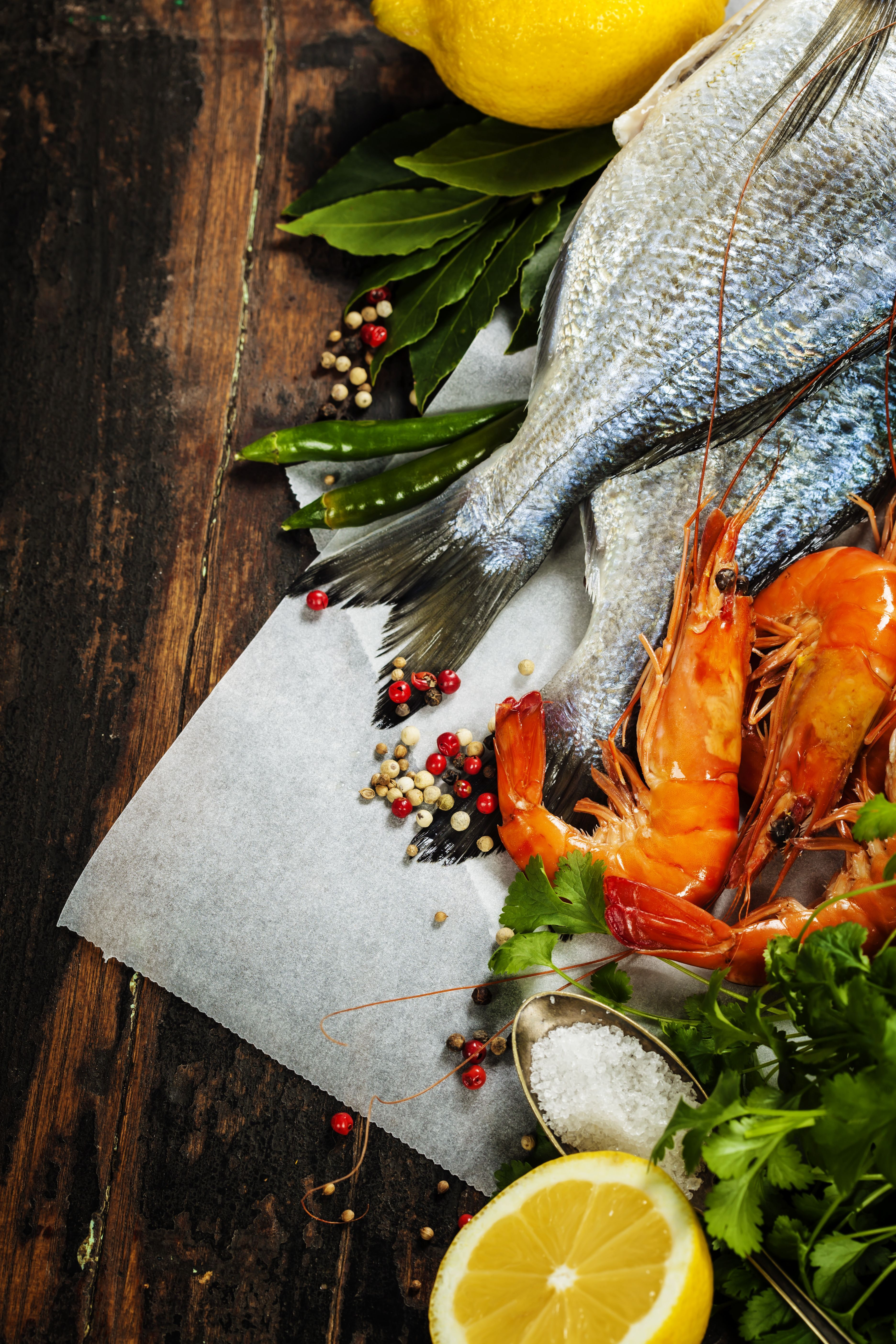 fresh dorado fish and shrimps on wooden board with ingredients- food and drink